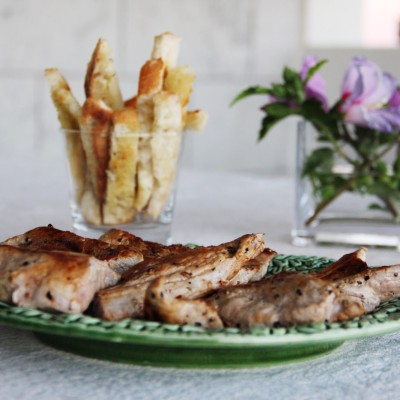 Lombinhos de porco com manteiga de ervas frescas e palitos de pão com azeite e orégãos